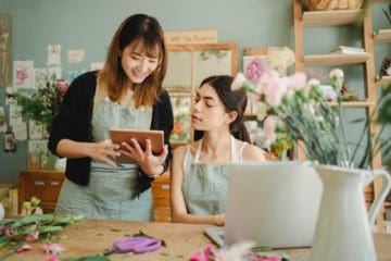 positive multiracial women with gadgets in floral shop